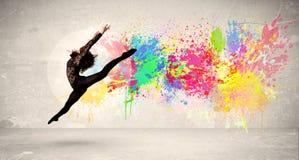Счастливый подросток скача с красочным splatter чернил на городском backg Стоковые Изображения RF