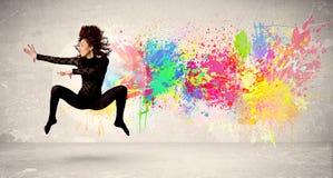 Счастливый подросток скача с красочным splatter чернил на городском backg Стоковая Фотография