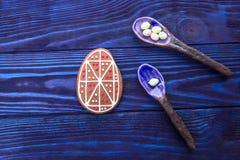 счастливый праздник Пряник пасхального яйца и керамические ложки на голубой предпосылке Стоковая Фотография