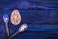 счастливый праздник Пряник пасхального яйца и керамические ложки на голубой предпосылке Стоковое Изображение