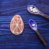 счастливый праздник Пряник пасхального яйца и керамические ложки на голубой предпосылке Стоковые Фото
