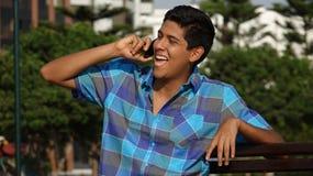 Счастливый предназначенный для подростков мальчик говоря на сотовом телефоне стоковое изображение rf