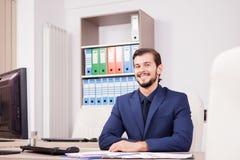 Счастливый предприниматель в деловом костюме на его месте работы Стоковое Изображение RF