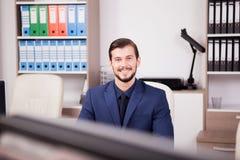 Счастливый предприниматель в деловом костюме на его месте работы Стоковые Изображения RF