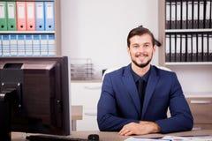 Счастливый предприниматель в деловом костюме на его месте работы Стоковое фото RF