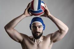 Счастливый профессиональный игрок водного поло держа шарик над его головой смотря камеру Стоковая Фотография RF
