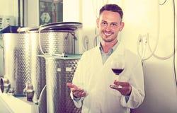 Счастливый работник винодельни держа бокал вина Стоковое фото RF