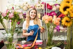 Счастливый работник окруженный цветками Стоковые Изображения RF