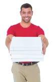Счастливый работник доставляющий покупки на дом давая коробки пиццы Стоковые Изображения