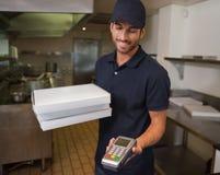 Счастливый работник доставляющий покупки на дом пиццы держа машину кредитной карточки стоковые изображения