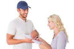 Счастливый работник доставляющий покупки на дом получая подпись от клиента Стоковая Фотография RF