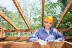 Счастливый рабочий-строитель держа молоток на месте Стоковые Фото
