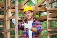 Счастливый рабочий-строитель держа молоток на месте Стоковые Фотографии RF
