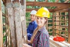 Счастливый рабочий-строитель с коллегой на месте Стоковая Фотография RF