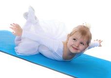 Счастливый радостный спортсмен маленькой девочки лежа на половике стоковые изображения rf