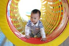 Счастливый ребенк имея потеху на спортивной площадке Стоковая Фотография