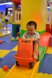 Счастливый ребенк имея потеху на спортивной площадке Стоковые Фото