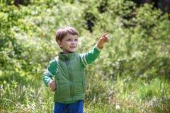 Счастливый ребенк наслаждаясь солнечным днем поздним летом и осени в природе на зеленой траве Стоковое фото RF