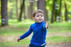 Счастливый ребенк наслаждаясь солнечным днем поздним летом и осени в природе на зеленой траве Стоковые Фото