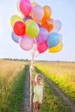 Счастливый ребенк ребенка маленькой девочки с воздушными шарами в поле Стоковые Изображения