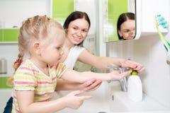 Счастливый ребенк с руками мамы моя в ванной комнате стоковое изображение