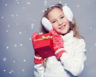 Счастливый ребенок в одеждах зимы с подарком Стоковые Изображения