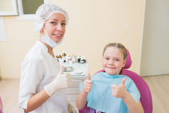 Счастливый ребенок в стуле дантиста при женский доктор показывая большие пальцы руки вверх на зубоврачебной клинике Стоковое Фото