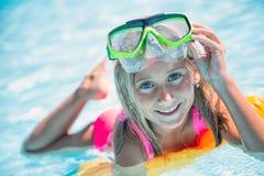 Счастливый ребенок девушки играя в бассейне на солнечный день Милая маленькая девочка наслаждаясь каникулами праздника Стоковое Фото