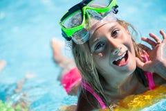 Счастливый ребенок девушки играя в бассейне на солнечный день Милая маленькая девочка наслаждаясь каникулами праздника Стоковые Фотографии RF