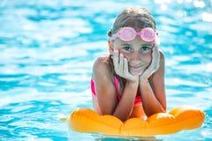 Счастливый ребенок девушки играя в бассейне на солнечный день Милая маленькая девочка наслаждаясь каникулами праздника Стоковое Изображение RF
