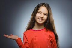 Счастливый ребенок держит в наличии что-то Портрет крупного плана красивый усмехаться девушки стоковые фото