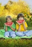 Счастливый ребенок есть арбуз в саде 2 мальчика с плодоовощ внутри Стоковая Фотография RF