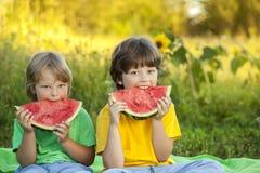 Счастливый ребенок есть арбуз в саде 2 мальчика с плодоовощ внутри Стоковое Изображение