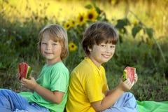 Счастливый ребенок есть арбуз в саде 2 мальчика с плодоовощ внутри стоковые изображения