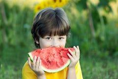Счастливый ребенок есть арбуз в саде Мальчик с плодоовощ outdoors Стоковое Изображение