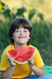 Счастливый ребенок есть арбуз в саде Мальчик с плодоовощ outdoors Стоковые Фото