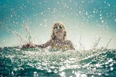 Счастливый ребенок играя в море Стоковое Изображение