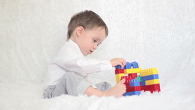 Счастливый ребенок играя в покрашенных блоках на кресле сток-видео