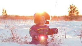 Счастливый ребенок играя в снеге на заходе солнца акции видеоматериалы
