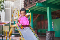 Счастливый ребенок играя на спортивной площадке Стоковая Фотография RF