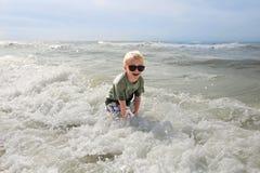 Счастливый ребенок играя снаружи в океанских волнах Стоковая Фотография