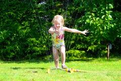 Счастливый ребенок играя с водой в саде Стоковое Фото