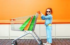 Счастливый ребенок маленькой девочки с тележкой и хозяйственными сумками вагонетки Стоковое Фото