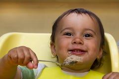 Счастливый ребенок младенца сидя в стуле с ложкой стоковые фотографии rf