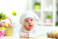 Счастливый ребенок младенца с ушами зайчика пасхи и яичками и цветками Стоковые Изображения RF