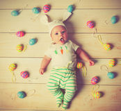 Счастливый ребенок младенца с ушами и яичками зайчика пасхи Стоковые Фотографии RF