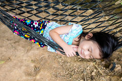 Счастливый ребенок наслаждаясь и ослабляя в гамаке, сладостной мечте и sm Стоковые Фотографии RF