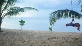 Счастливый ребенок отбрасывая на качании на пляже остров тропический видеоматериал