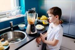 Счастливый ребенок подготавливая коктеиль плодоовощ в кухне Стоковое фото RF