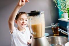Счастливый ребенок подготавливая коктеиль плодоовощ в кухне Стоковое Фото
